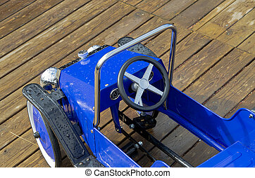 Blue toy vehicle - Old pedal car for children to play with.