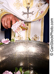 baptism ceremony - priest add oil on a bowl at an orthodox...
