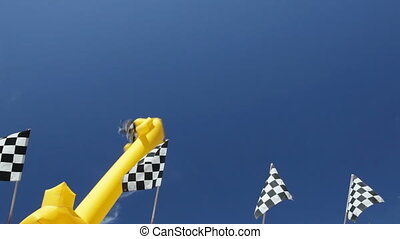 Dancing inflatable figure and checkered flags against blue...
