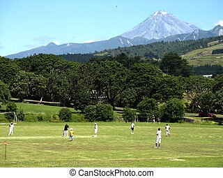 Mt Taranaki - cricket players under volcanoe Mt Taranaki,...