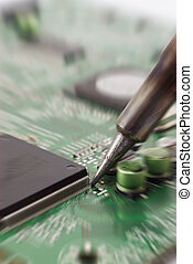 Circuit repair zoomed. - Technician repairing electronic...