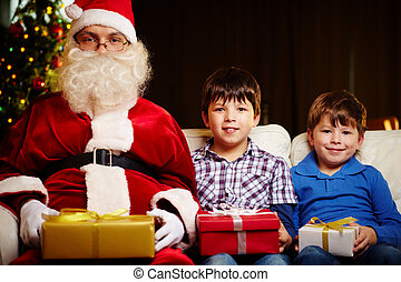 Christmas day - Photo of cute boys and Santa Claus holding...