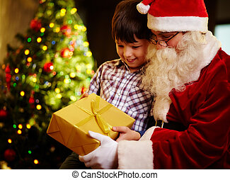 Looking at gift - Photo of cute boy and Santa Claus holding...