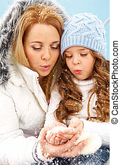 Snow fun - Portrait of mother and her daughter blowing snow...