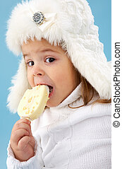 Eating ice-cream - Little girl in white furry hat eating...