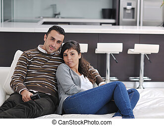 Relaxed young couple watching tv at home in bright living...