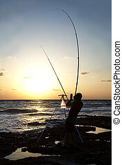 Fisherman at dawn - Fisherman silhouetted against the...