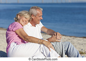 Happy Romantic Senior Couple Sitting Together on Beach