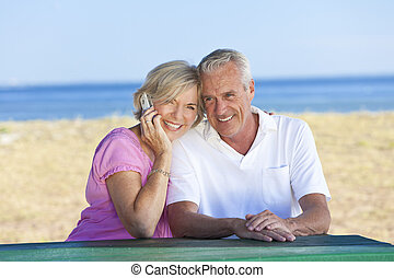 Happy Senior Couple Using Cell Phone at Table By Beach