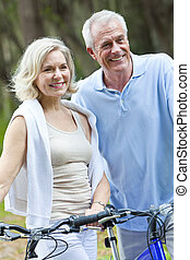 Happy Senior Man & Woman Couple Cycling Bicycles - Happy...