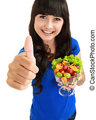 Portrait of a smiling woman with a bowl of fruit salad wishing you luck in isolated background