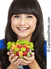 Closeup of a pretty young lady eating fruit salad in...
