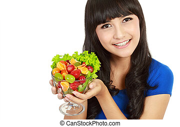Closeup portrait of a happy young lady eating fruit salad,
