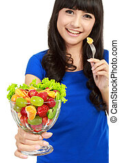 Pretty girl eating fruit salad, healthy fresh breakfast, dieting and health care concept. in white background