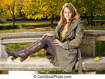 Beautiful young woman in the park at fall - Full figure...
