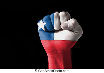 Fist painted in colors of chile flag - Low key picture of a...