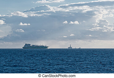 LNG carrier passing oil field