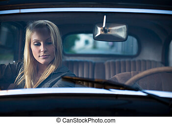 Portrait of a beautiful young blond in a vintage car. -...