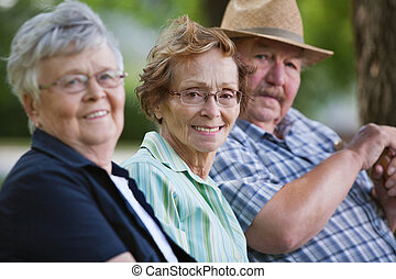 Senior friends sitting together in park - Portrait of senior...