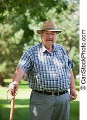 Senior man standing in park - Portrait of senior man...