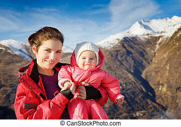 Mother with baby in sport costumes