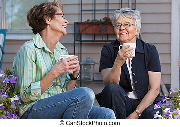 Women having cup of tea - Senior female friends enjoying cup...