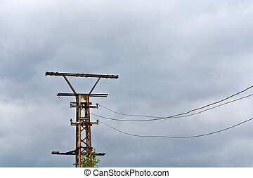 old rusty electrical tower with dark clouds