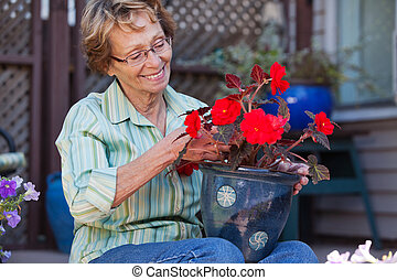Woman looking at flower pot - Cheerful senior woman looking...