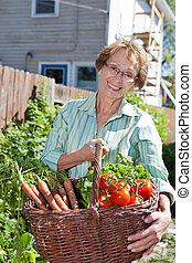 Senior woman holding basket full of vegetables
