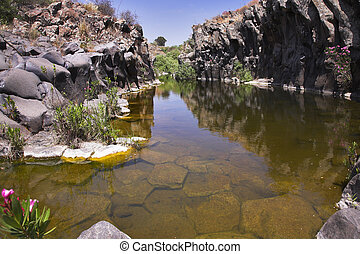 Drying up stream between picturesque stone polyhedrons in...
