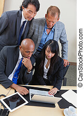 Business team working on laptop together