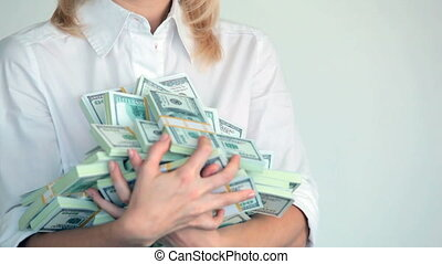 Earnings - Happy blonde holding heap of dollar bills in her...