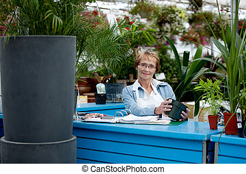 Senior Worker in Garden Center - Portrait of a senior woman...