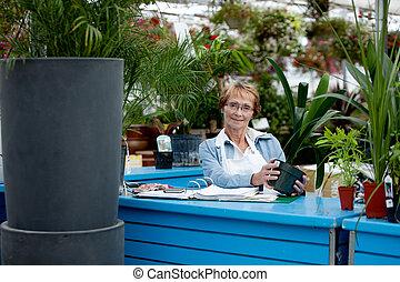Senior Worker in Garden Center - Portrait of a senior woman...