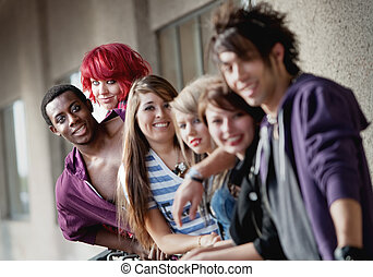 Punk rock looking teens smile at the camera as the camera...