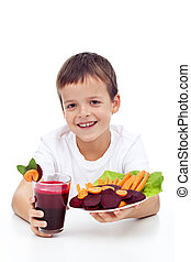 Healthy child with fresh betroot juice and vegetable slices