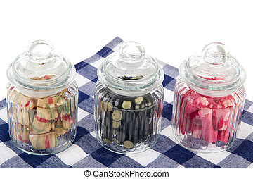 Candy jars - Three filled glass candy jars isolated over...