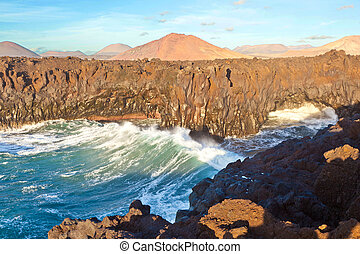 Steilküste mit Wellen und Bergen - Los Hervideros, coastline...
