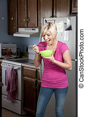 Woman Eating - A beautiful woman eating food from a bowl