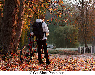 Woman cyclist with bike and backpack in autumn park, lit morning sun