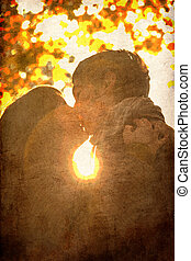 Couple kissing in the park at sunset.
