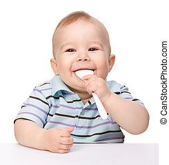 Cute little boy is biting spoon