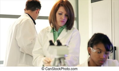 Lab Tech Looks into Microscope - An attractive technician or...