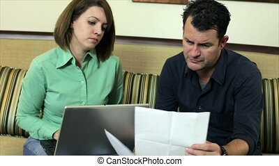 Couple Going Over Bills - A couple sitting in their living...