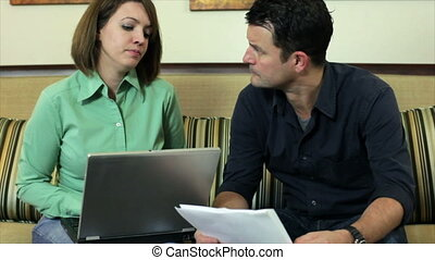 Couple fighting over bills - A couple sitting in their...
