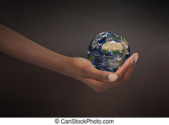 Feminine hand holding the Earth against a dark background