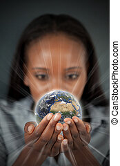 Woman holding a glowing Earth against a dark background