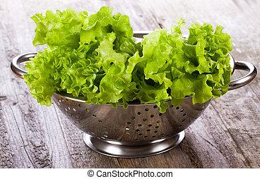 lettuce salad in metal colander on wooden table
