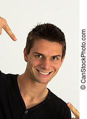 Young man smiling and pointing at himself with success