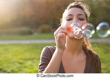 Blowing bubbles into the wind - Beautiful young brunette...